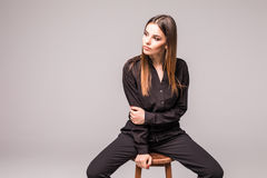 Portrait of a happy cheerful woman in black sitting on the chair and looking at camera over gray background Stock Photos