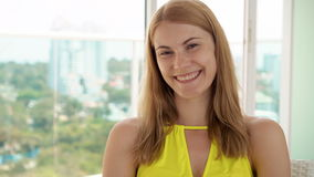 Portrait of happy cheerful woman sitting on balcony enjoying the view. Park and city landscape behind stock video footage