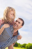 Portrait of Happy and Cheerful Young Caucasian Couple Piggybacki Royalty Free Stock Image