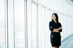 Attractive smiling young business woman. Portrait of happy cheerful young lady with crossed arms on business center window backgro royalty free stock photos