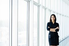 Attractive smiling young business woman. Portrait of happy cheerful young lady with crossed arms on business center window backgro stock photography