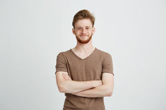 Portrait of happy cheerful young man with beard smiling looking at camera with crossed arms over white background. Stock Image