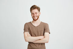 Portrait of happy cheerful young man with beard smiling looking at camera with crossed arms over white background. Copy space royalty free stock images