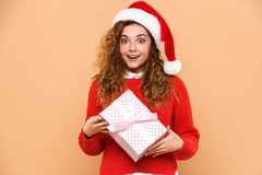 Portrait of a happy cheery girl. Dressed in santa hat holding gift box  over beige background Royalty Free Stock Photography