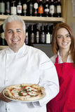 Portrait of a happy chef holding pizza with beautiful waitress Stock Image