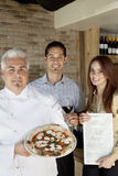 Portrait of happy chef holding pizza with young couple Royalty Free Stock Photos