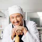 Portrait Of Happy Chef Leaning On Rolling Pin Royalty Free Stock Photos