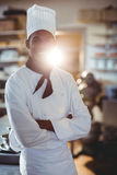 Portrait of happy chef standing with arms crossed. In commercial kitchen stock photography
