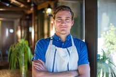 Portrait of happy chef standing with arms crossed. In restaurant stock photography