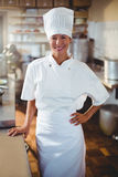 Portrait of happy chef standing with hand on hip. Portrait of happy chef standing in kitchen with hand on hip royalty free stock image