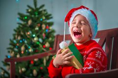 Portrait of a happy child with a gift on the background of a Christmas tree Royalty Free Stock Image