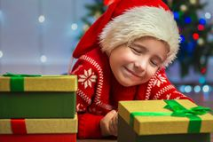 Portrait of a happy child with a gift on the background of a Christmas tree Stock Images