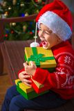 Portrait of a happy child with a gift on the background of a Christmas tree Stock Photos