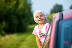 Portrait of happy child girl sticking their head out the car win Royalty Free Stock Image