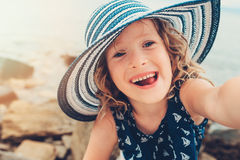 Portrait of happy child girl in stripe hat playing and making selfie on the beach Stock Photo