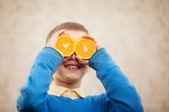 Portrait Happy child holding orange before his eyes like in sunny day. Portrait Happy child holding orange before his eyes like in sunny day Royalty Free Stock Image