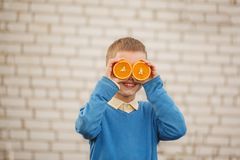 Portrait Happy child holding orange before his eyes like in sunny day. Portrait Happy child holding orange before his eyes like in sunny day Stock Image
