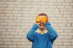 Portrait Happy child holding orange before his eyes like in sunny day. Portrait Happy child holding orange before his eyes like in sunny day Royalty Free Stock Images