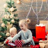 Portrait of happy child looking at decorative toy ball by Christmas tree. Kid enjoy the holiday. Happy little child stock photography