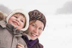 Portrait of happy child and mother. In winter time Stock Image