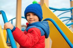 Portrait of happy child outdoors. Cute little boy playing on colorful modern playground. Child have fun in cold time. Happy and stock images