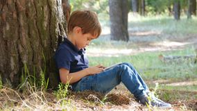 Portrait of a happy child playing in a tablet. A little boy sitting by a tree in the park. Modern technologies stock video footage