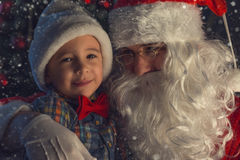 Portrait of a happy child with Santa Claus next to Christmas tree Stock Images