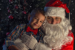Portrait of a happy child with Santa Claus next to Christmas tree Stock Image