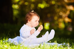 Portrait of happy child sitting on the meadow and holds snack in the park. Stock Photo