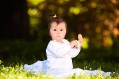 Portrait of happy child sitting on the meadow and holds snack in the park. Stock Images