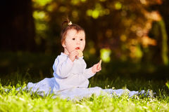 Portrait of happy child sitting on the meadow and holds snack in the park. Portrait of happy joyful child sitting on the meadow and holds snack in the park Royalty Free Stock Images