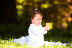 Portrait of happy child sitting on the meadow and holds snack in the park. Portrait of happy joyful child sitting on the meadow and holds snack in the park Royalty Free Stock Image