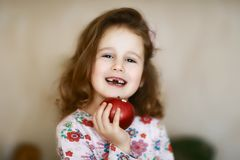 Portrait of a happy child who has lost milk teeth, cute little curly toothless caroque girl smiles and holds in her hand a red stock image