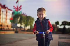Portrait of the happy child who rides the scooter Stock Images