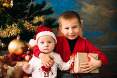 Portrait of happy children with Christmas gift boxes and decorations. Two kids having fun at home Stock Photos