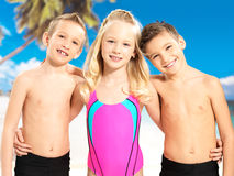 Portrait of the happy children enjoying at beach. Schoolchild kids standing together in bright color swimwear Stock Photos