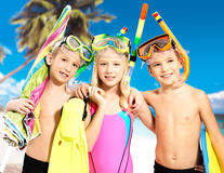 Portrait of the happy children enjoying at beach. Schoolchild kids standing together in bright color swimwear with swimming mask on head Royalty Free Stock Photos