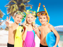 Portrait of the happy children enjoying at beach. Schoolchild kids standing together in bright color swimwear with swimming mask on head Stock Image