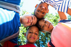 Portrait of happy children forming huddle Royalty Free Stock Image