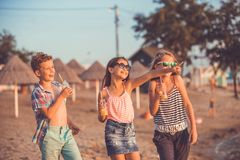 Portrait of happy children while having fun walking on the beach at the day time royalty free stock photos