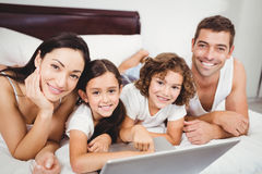 Portrait of happy children with parents using laptop on bed Royalty Free Stock Images
