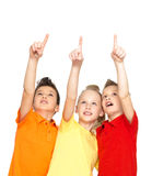 Portrait of the happy children point up by finger - isolated on. Portrait of the happy children point up by fingers on something away - isolated on white stock images