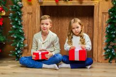 Portrait of happy children with presents around the Christmas tr. Ee by the fireplace Stock Image