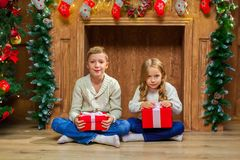 Portrait of happy children with presents around the Christmas tr. Ee by the fireplace Royalty Free Stock Photography