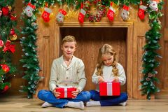 Portrait of happy children with presents around the Christmas tr. Ee by the fireplace Royalty Free Stock Image