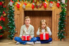 Portrait of happy children with presents around the Christmas tr. Ee by the fireplace Royalty Free Stock Images