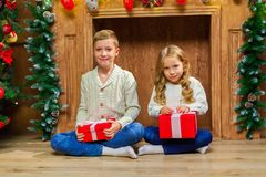 Portrait of happy children with presents around the Christmas tr. Ee by the fireplace Stock Photo