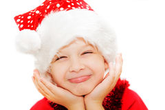 Portrait of a happy christmas child in santa hat on the light ba Royalty Free Stock Photography