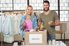 Portrait of happy colleagues smiling while holding products. From donation box stock photos