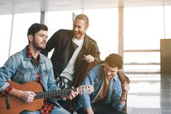 Cheerful male performing melody inside. Portrait of happy comrades singing song. Smiling young male playing guitar indoor. Amity concept Stock Images